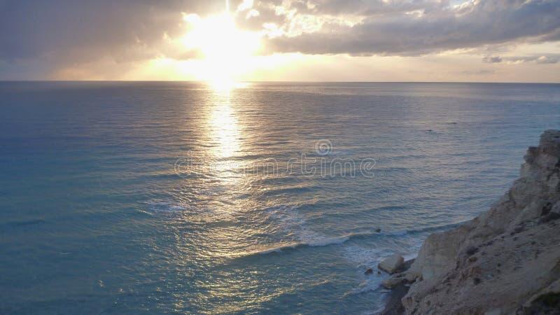 Bello tramonto romantico ad una spiaggia rocciosa fotografia stock libera da diritti