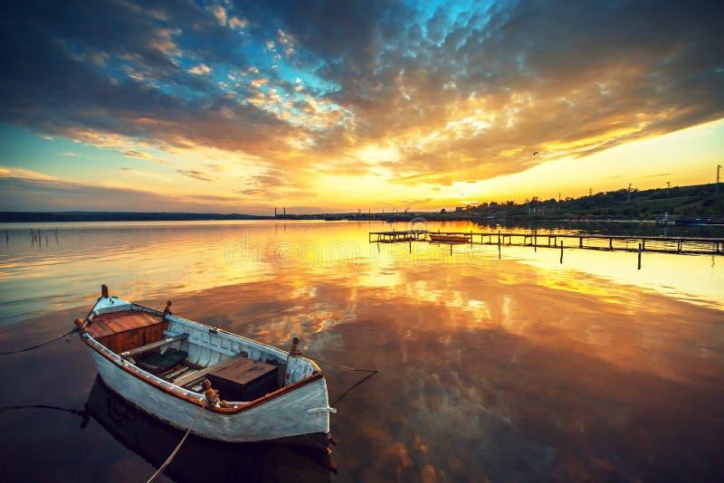 Bello tramonto sopra il lago calmo e una barca con il cielo che riflette i fotografie stock libere da diritti