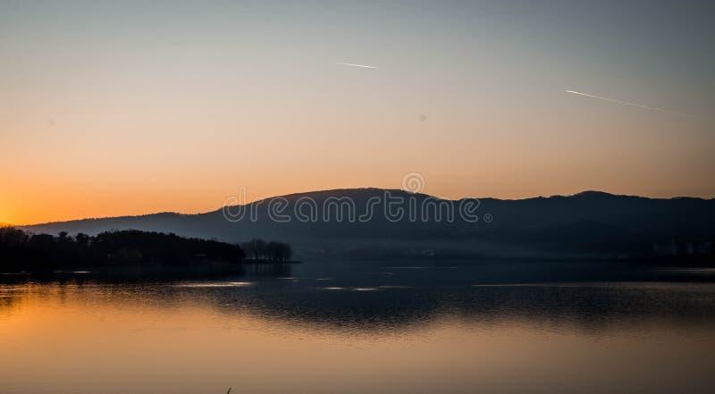 Bello tramonto sopra il lago con il fondo della siluetta dell'albero fotografia stock libera da diritti