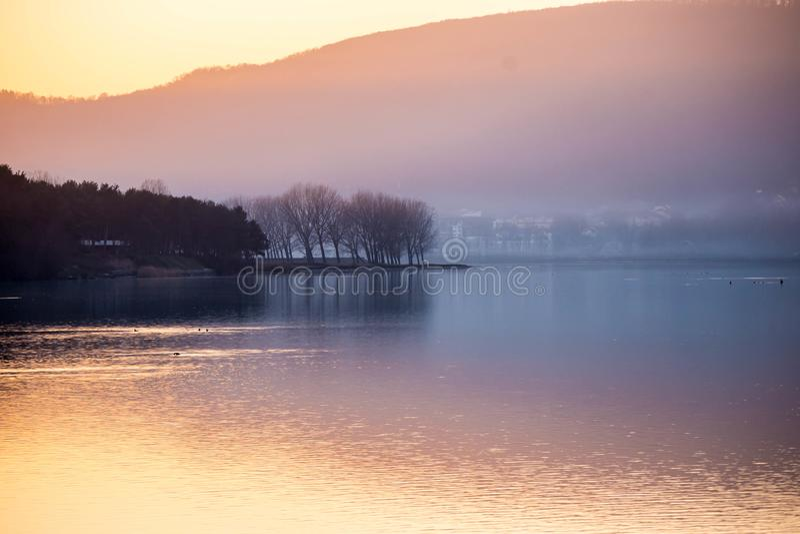 Bello tramonto sopra il lago con il fondo della siluetta dell'albero fotografie stock libere da diritti