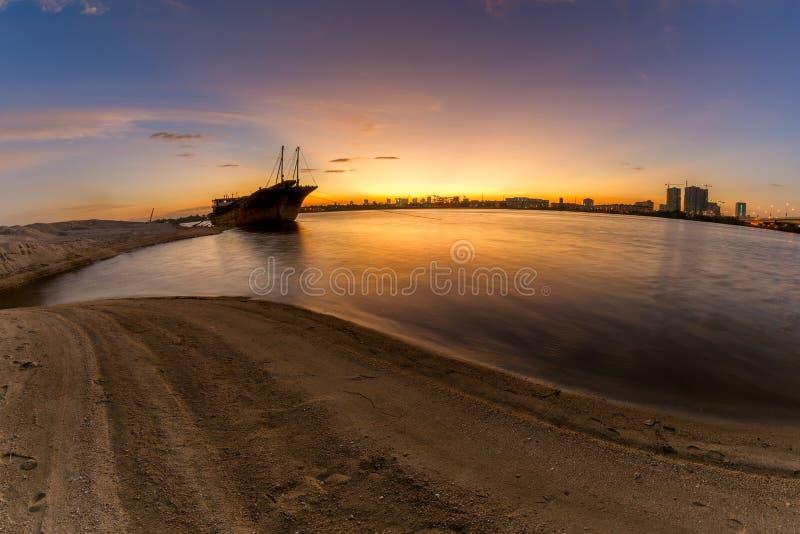 Bello tramonto sopra la spiaggia con la nave incagliata fotografie stock libere da diritti
