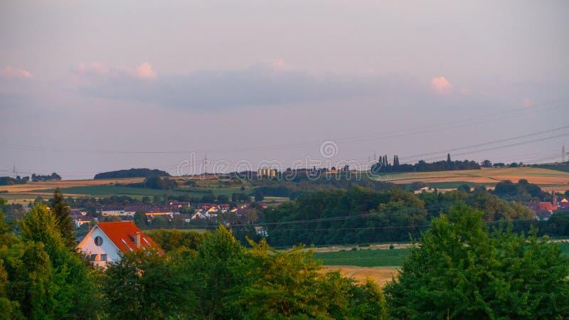 Bello tramonto sopra un campo e una cittadina in Germania immagine stock