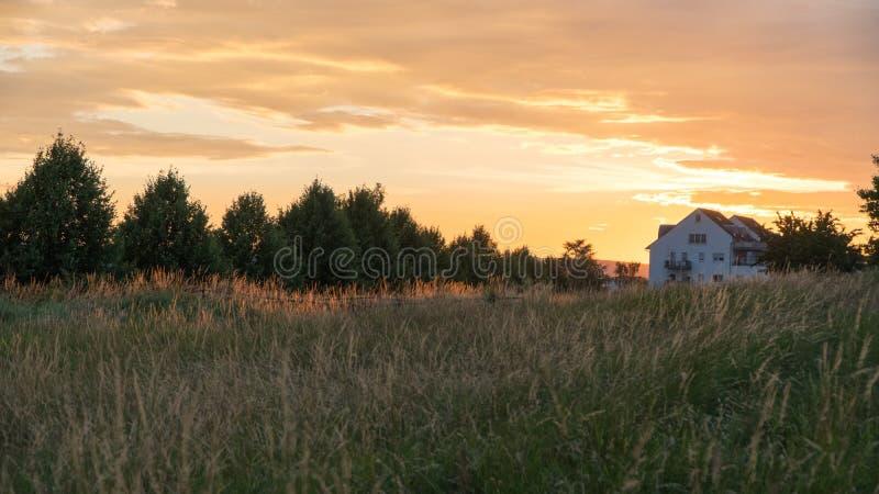 Bello tramonto sopra un campo e una cittadina in Germania fotografia stock libera da diritti