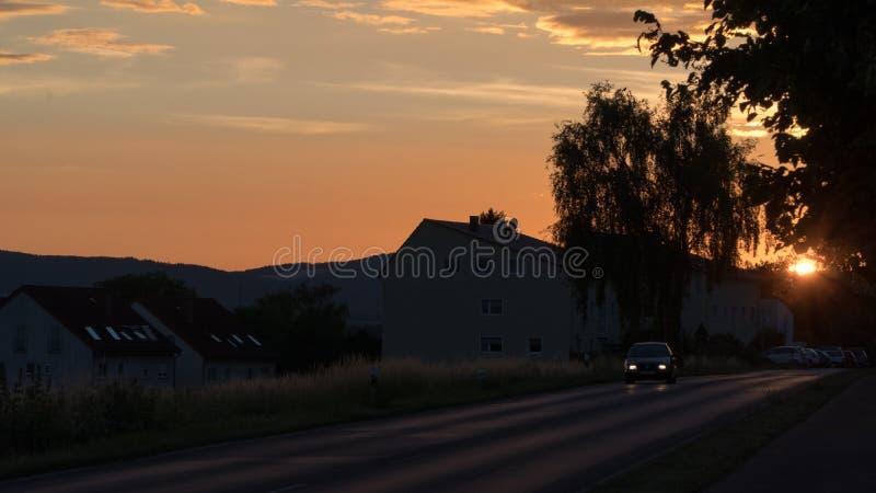 Bello tramonto sopra un campo e una cittadina in Germania fotografia stock