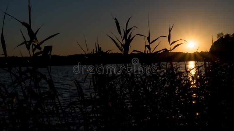 Bello tramonto sul lago, pescatori sulla barca immagine stock