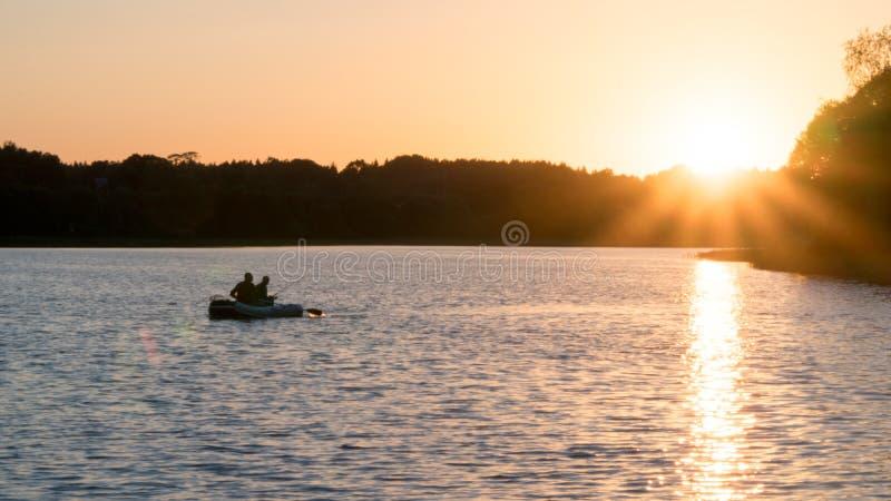 Bello tramonto sul lago, pescatori sulla barca fotografia stock
