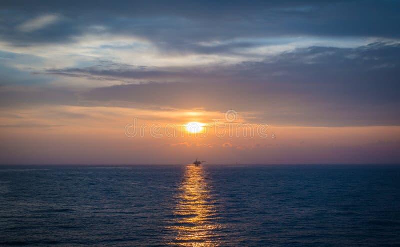 bello tramonto sull'oceano con la piattaforma del gas e del petrolio marino, immagine stock libera da diritti
