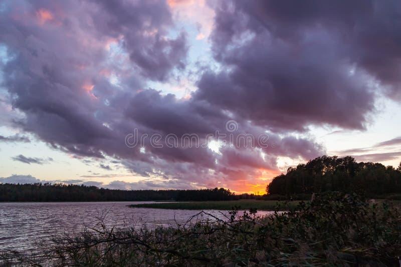 Bello tramonto variopinto sul lago, luce solare attraverso le nuvole drammatiche, uguaglianti il paesaggio di estate - foto, imma fotografie stock