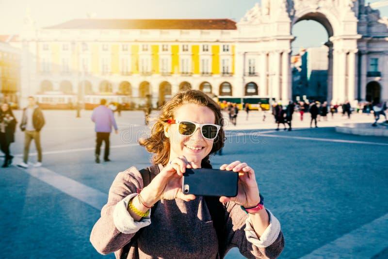 Bello turista della giovane donna a Lisbona che fa foto sul cellulare pH fotografia stock