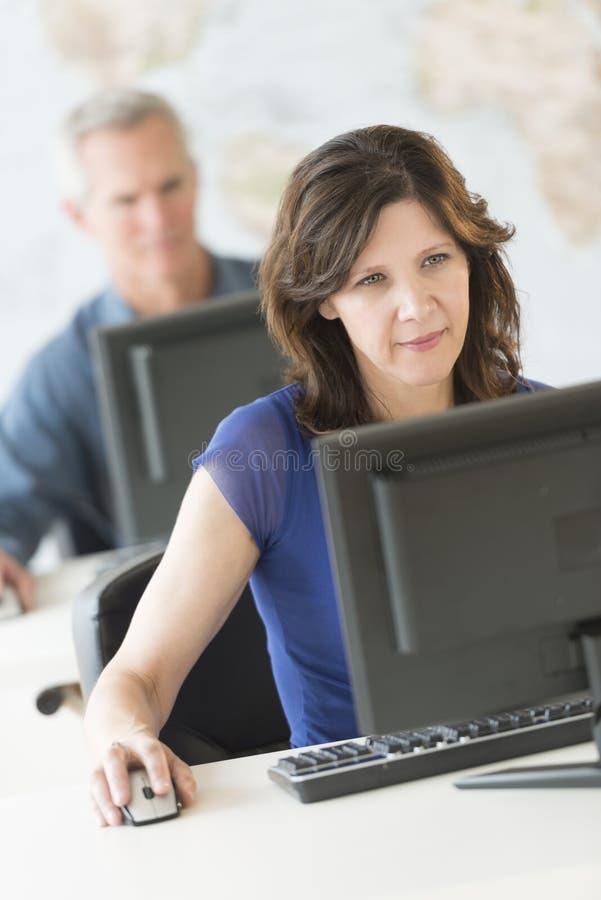 Bello ufficio di Using Computer In della donna di affari fotografie stock libere da diritti