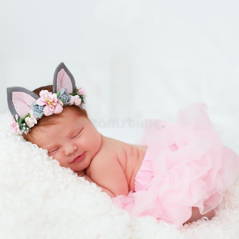 Bello, una ragazza di neonato settimane di età sorridenti, nella gonna rosa del tutu e nella banda capa floreale fotografia stock