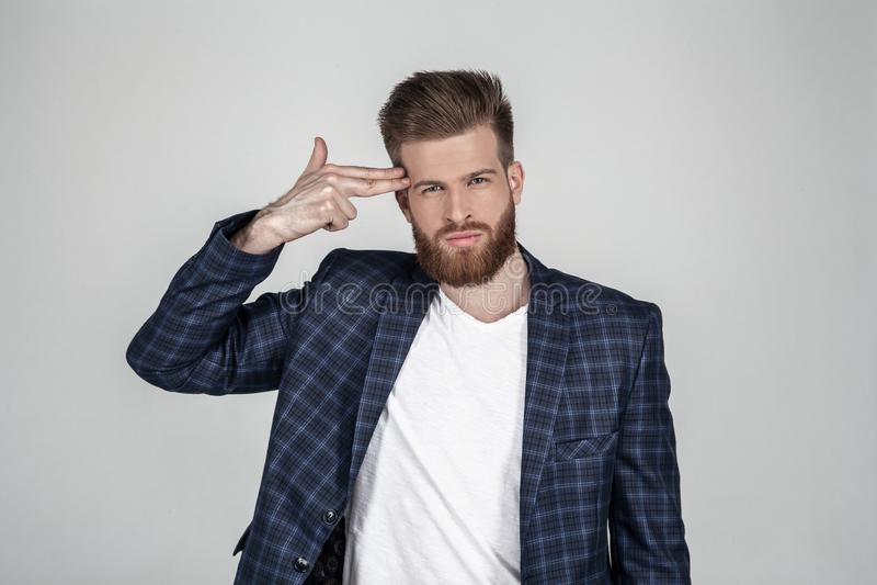 Bello uomo barbuto sexy con un bello stile di capelli tiene la sua mano alla sua testa come se sia una pistola e vuole uccidersi immagine stock