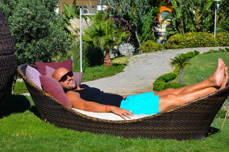 Bello uomo che si rilassa in un giardino tropicale fotografia stock