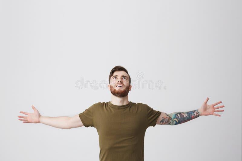 Bello uomo europeo barbuto con il braccio ed i capelli scuri tatooed in mani di diffusione della maglietta verde oliva casuale am immagine stock libera da diritti