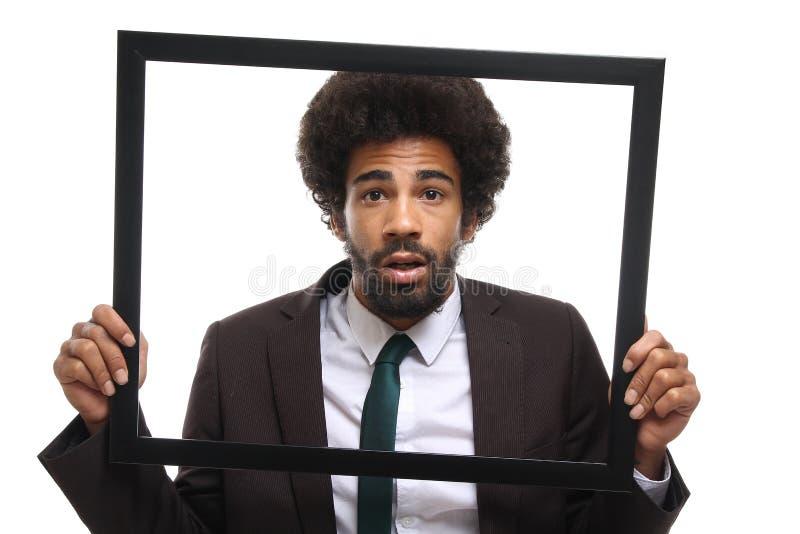 Bello uomo funky felice di afro che posa davanti ad un fondo immagine stock