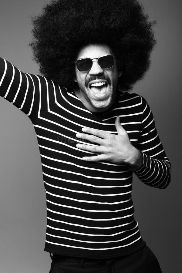Bello uomo funky felice di afro che posa davanti ad un fondo fotografie stock