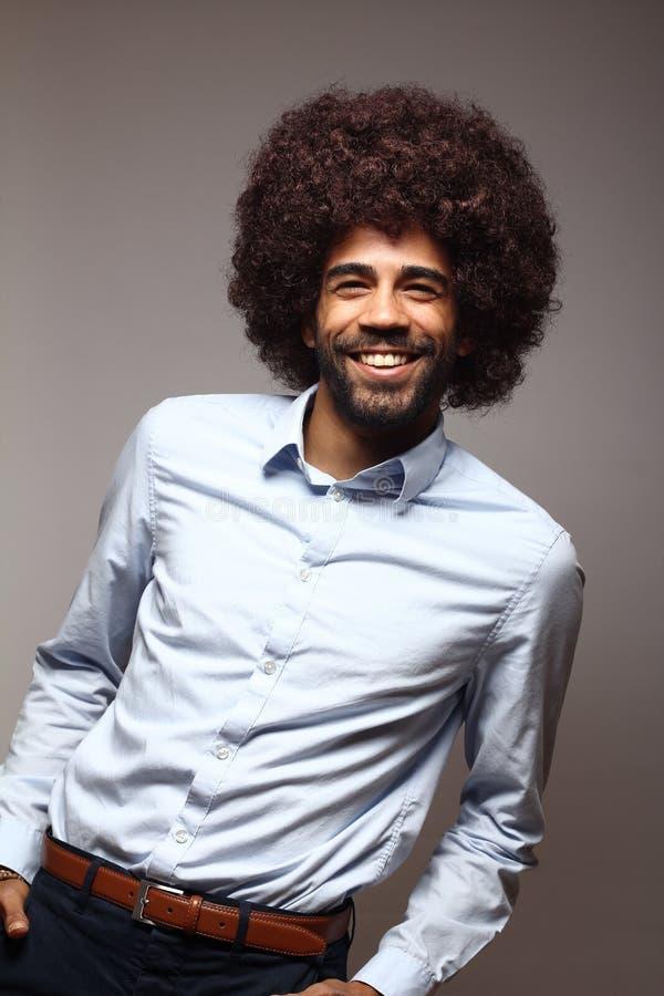 Bello uomo funky felice di afro che posa davanti ad un fondo fotografia stock