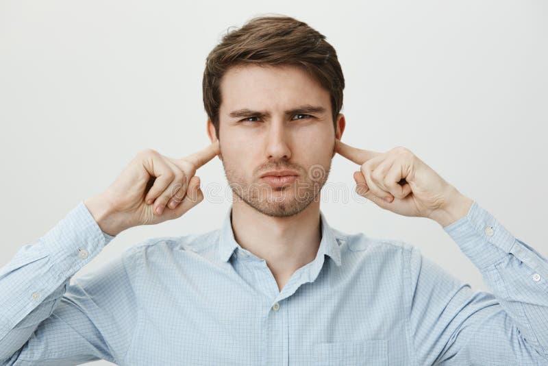 Bello uomo infastidito nelle orecchie della copertura della camicia con i dito indice e nello strabismo con l'espressione seria,  immagine stock