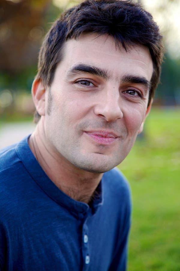 Uomo bello serio che sorride nel parco fotografia stock libera da diritti