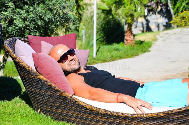 Bello uomo sorridente abbronzato muscolare con gli occhiali da sole che posano e che si rilassano in un giardino tropicale immagine stock