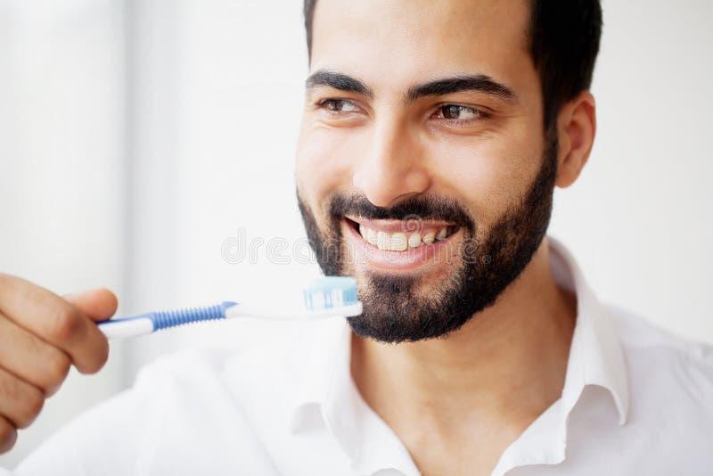 Bello uomo sorridente che pulisce i denti bianchi sani con la spazzola H fotografia stock libera da diritti