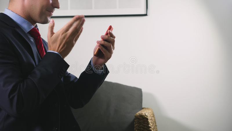 Bello uso gay uno smartphone cellulare mentre sedendosi nel salone nella sera Giovane sorridente felice fotografia stock libera da diritti