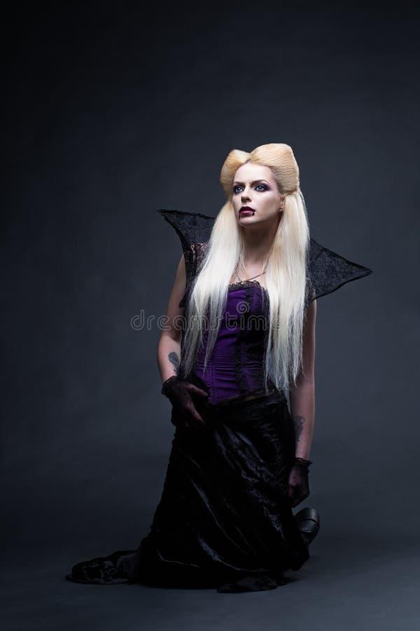 Bello vampiro biondo della ragazza che sta sulle ginocchia immagine stock libera da diritti