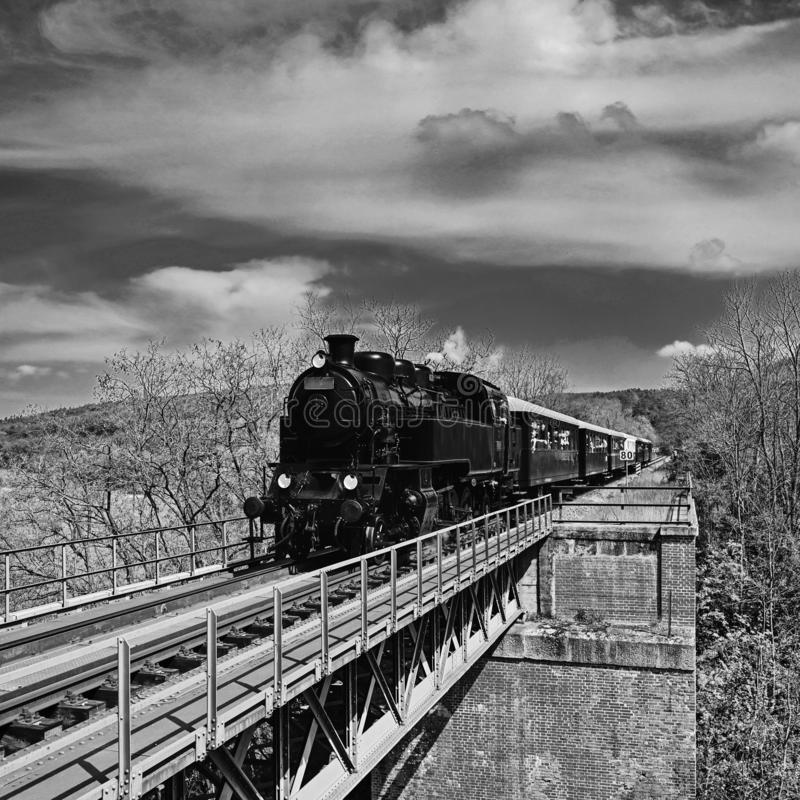 Bello vecchio treno a vapore che guida lungo un ponte nella campagna Concetto per il viaggio, il trasporto ed il retro vecchio st fotografie stock libere da diritti