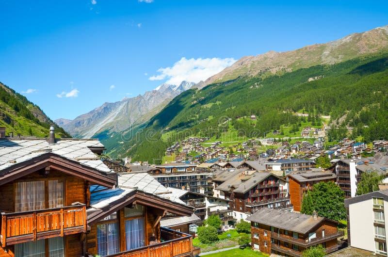 Bello villaggio Zermatt in alpi svizzere con i suoi chalet tipici fotografati di estate Montagne nella priorit? bassa Vista panor immagini stock