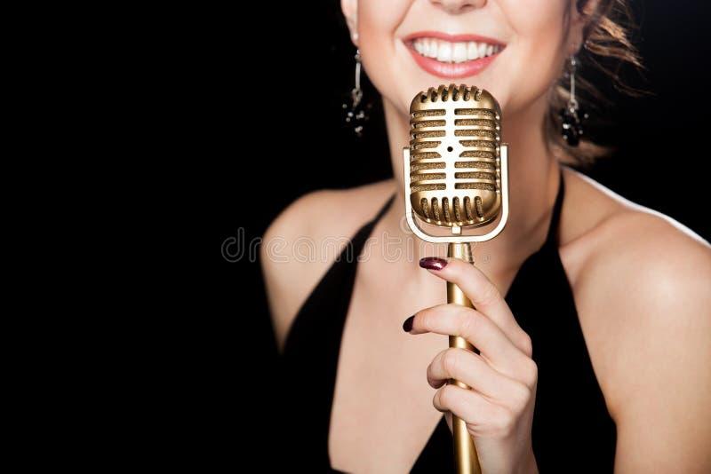 Bello vocalist della ragazza con il sorriso che tiene microp d'annata dorato fotografia stock
