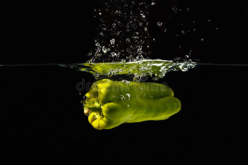 Bellpepper vert tombant dans l'eau avec une éclaboussure photo stock