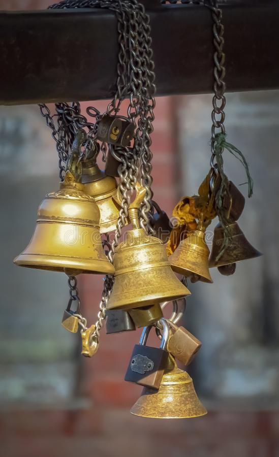 Bells on chain at Swayambhunath Temple aka Monkey Temple, Kathmandu, Nepal. Gold colored bells at Swayambhunath Temple aka Monkey Temple, Kathmandu, Nepal stock image
