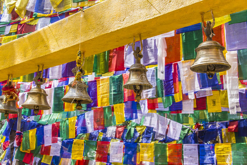 Bells and prayer flags. Prayer bells in a buddhist temple in Darjeeling, India, and colorful buddhist prayer flags in the background stock photography