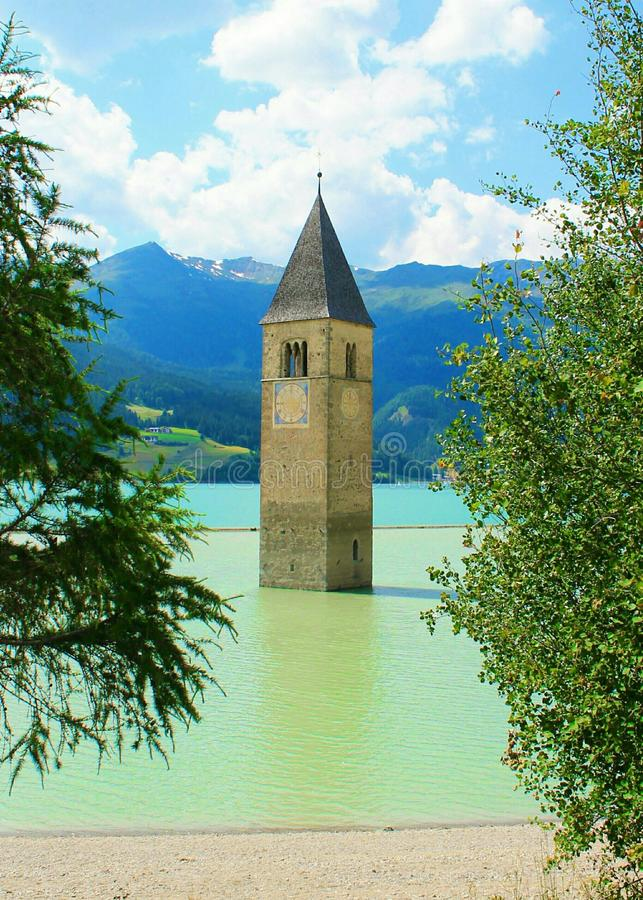Belltower in the lake. Submerged belltower in a south tyrolean lake royalty free stock images