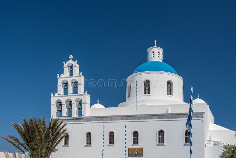 Belltower och blå kupol på grekisk ortodox kyrka i Oia royaltyfria bilder