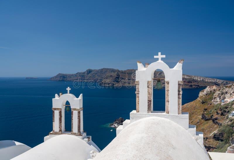 Belltower och klockor på grekisk ortodox kyrka i Oia royaltyfria bilder