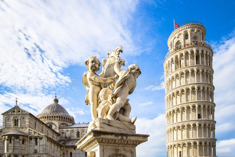 Leaning Tower of Pisa and the Fontana dei Putti, Italy. The Belltower of Pisa, and wonderful medieval monument - the Fontana dei Putti Fountain with Angels with royalty free stock images