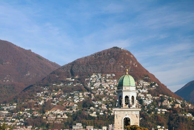 Belltower y montañas Lugano, Suiza fotografía de archivo libre de regalías