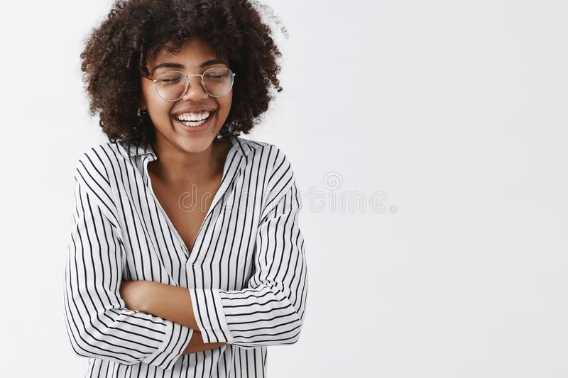 Belly aching from laughter. Amused and carefree attractive african american woman in striped blouse and glasses closing stock photography