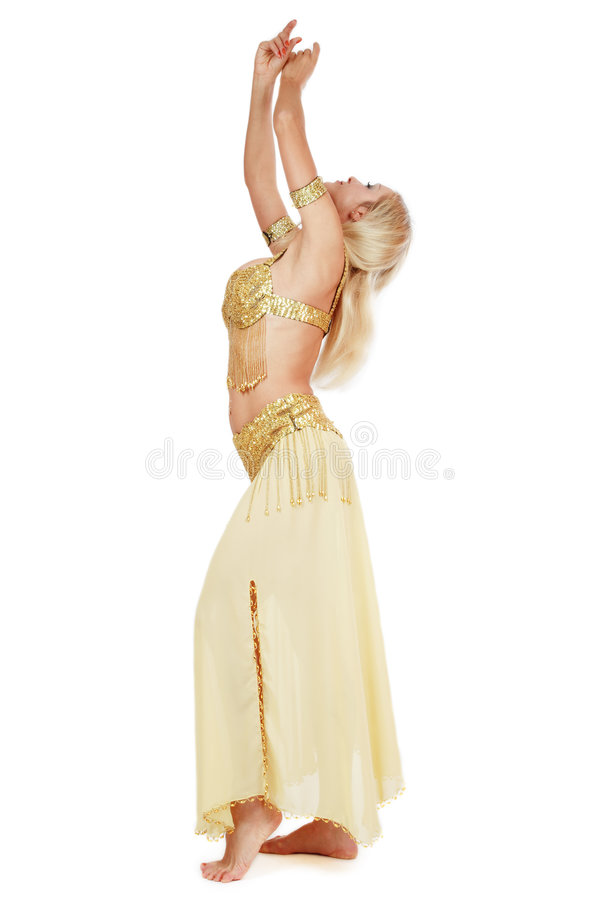 Belly-dancer. Beautiful blond bellydancer in golden costume dancing with hands up, over white background stock photo