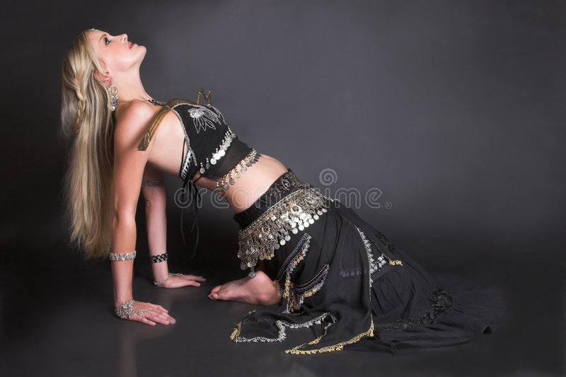 Belly Dancer. Balancing a tribal sword on her body stock images