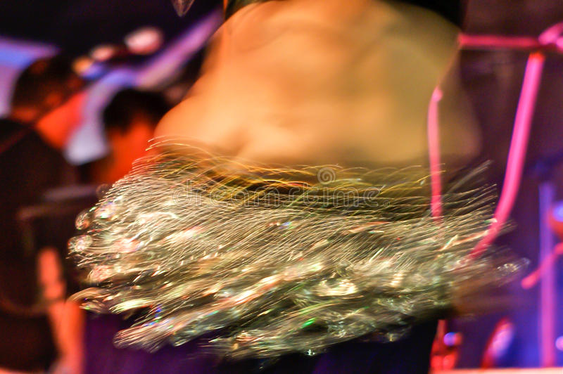 Belly Dancer. Action shot of the torso of a female belly dancer shaking her hips. She is wearing a coin belt stock image
