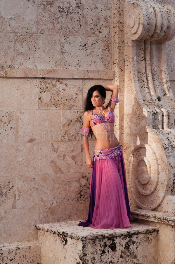 Belly Dancer in Pink Costume. A full length shot of a beautiful belly dancer wearing a pink costume and posing on a stone structure with Mediterranean style royalty free stock photo