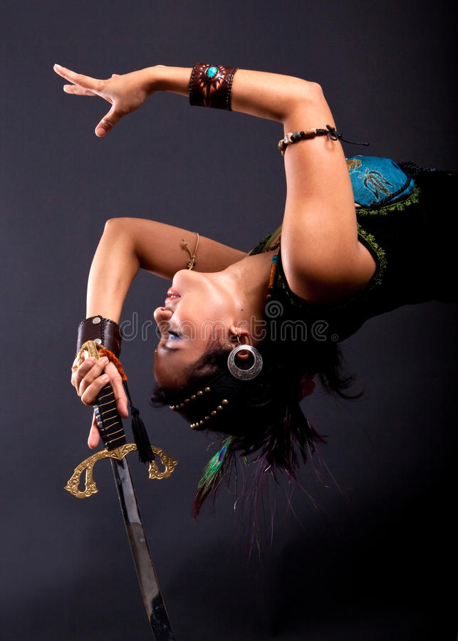 Belly dancer with sword. Belly dancer performing a sword dance royalty free stock photography