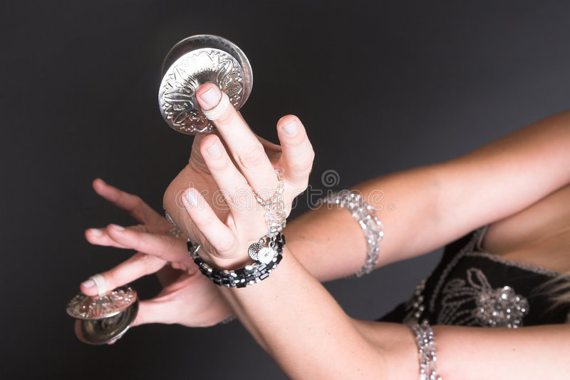 Belly Symbals. Belly Dancer hands holding Tribal Zagat or finger symbols royalty free stock photography