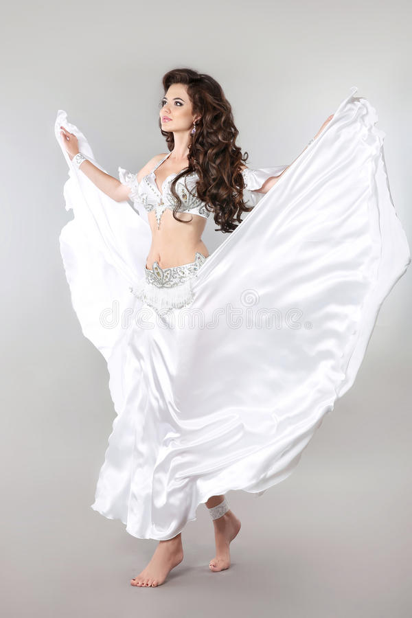 Bellydance. Arabian Woman Bellydancer isolated on studio background, oriental brunette girl dancer with perfect body and lon royalty free stock image