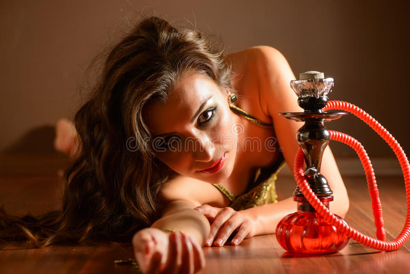 Bellydancer posing with hookah. Beautiful belly dancer wearing a black belly dance costume. She is lying on the floor with a hookah pipe royalty free stock photo