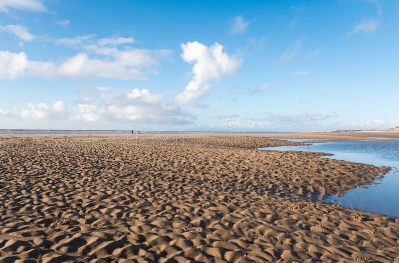 Belo céu azul e areia texturizada, num dia legal de Invernos ensolarados na praia fotos de stock royalty free