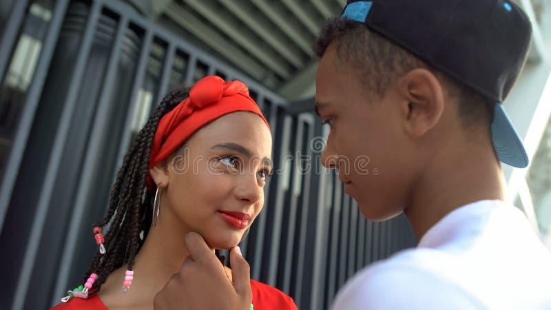 Belo casal de adolescentes afro-americanos tentando beijar, sentimentos românticos foto de stock royalty free