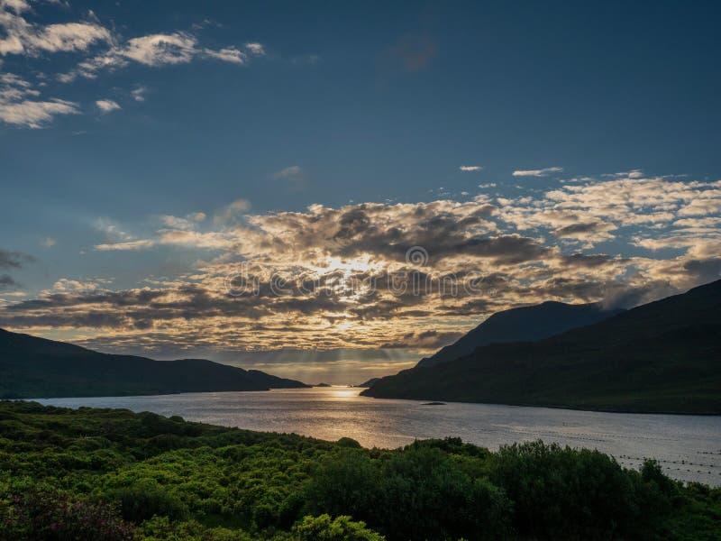 Belo e dramático céu por terra sobre o fiorde de Killary, condado Galway Raios do sol brilham pelas nuvens Calma e humor tranquil fotografia de stock royalty free